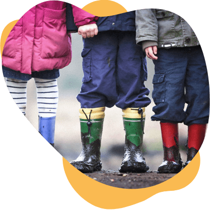 Three children wearing coats and rain boots standing toegther.