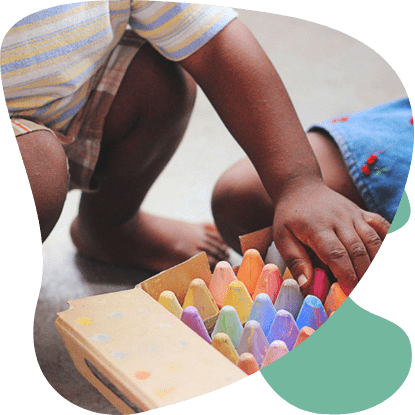 A child using brightly colored chalk.